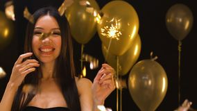 Smiling Asian female with bengal light standing under falling confetti, party. Stock footage stock footage