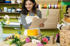 Smiling asian female florist making notes at flower shop counter Royalty Free Stock Photography