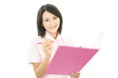 Smiling Asian female nurse. Portrait of an Asian female nurse Royalty Free Stock Photos