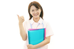 Smiling Asian female nurse with thumbs up Royalty Free Stock Images