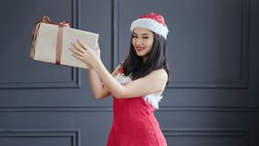 Smiling Asian female Santa Claus holding big carton gift box with bow at studio in gray background. Attractive young Christmas Korean woman enjoying having