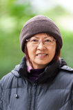 Smiling Asian female senior in winter clothes Stock Image