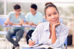 Smiling Asian female student. Portrait of smiling Asian female student studying at desk in classroom Stock Image