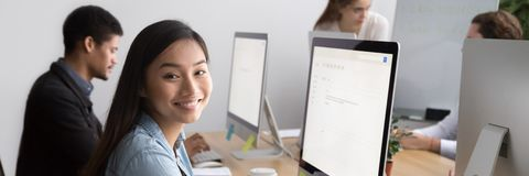Horizontal photo asian employee looking at camera sitting at workplace. Smiling asian female worker looking at camera sitting at workplace working on pc with stock photography