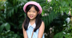 Smiling Asian Girl. Child Gets Ready for Traveling. Kid Laughing with Happiness. Happy Asian girl, child or kid, smiling and getting ready for traveling stock video footage