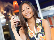 Smiling asian girl enjoying a soda on terrace Stock Photos