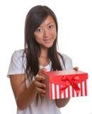 Smiling asian girl has a present Royalty Free Stock Photos