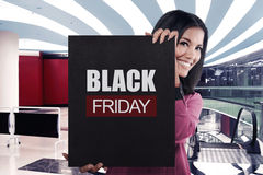 Smiling asian girl holding black banner sale with BLACK FRIDAY m Stock Photo