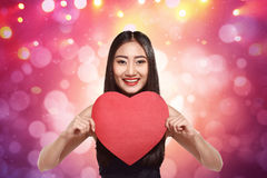 Smiling asian girl holding red heart shape Royalty Free Stock Photos