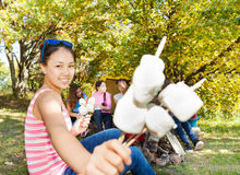 Smiling Asian girl holding sticks with marshmallow Stock Photos