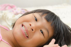 Smiling Asian girl lay down on bed Royalty Free Stock Photo