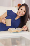 Smiling asian girl lying on the sofa reading a novel and drinkin Stock Photo