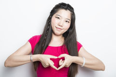 Smiling asian girl over a white background doing a heart shape w Stock Photos