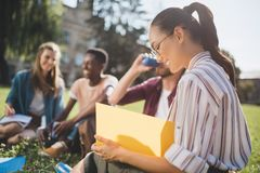 Multiethnic students studying together. Smiling asian girl preparing for exam while multiethnic friends sitting behind on grass Royalty Free Stock Photography