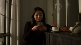 Smiling asian girl typing message on smart phone. Smiling charming asian young woman typing message on smart phone while enjoying lesire in the evening at home stock video footage