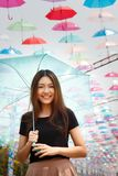 Smiling Asian girl with umbrellas Stock Images