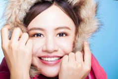 Smiling asian girl with winter wear sweater.isolated on blue bac Royalty Free Stock Photography