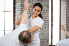 Smiling Asian instructor looking on his client. Do it slowly. Positive delighted longhaired men wearing white T-shirt stretching arm of his visitor during Royalty Free Stock Images