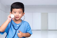 Smiling Asian kid in blue medical uniform holding stethoscope lo. Oking at camera, healthy concept idea stock images