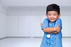 Smiling Asian kid in blue medical uniform holding stethoscope lo. Oking at camera, healthy concept idea royalty free stock photography