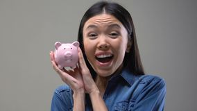 Smiling Asian lady shaking piggy bank, money saving tips, finance and budget