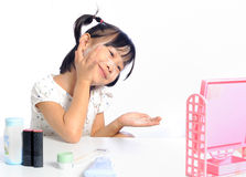 Smiling asian little girl is applying make up baby powder her fa Royalty Free Stock Image