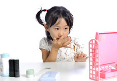 Smiling asian little girl is applying make up baby powder her fa Stock Image