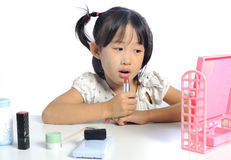Smiling asian little girl is applying make up baby powder her fa Royalty Free Stock Photography