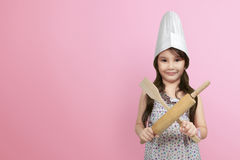 Smiling asian little girl in chef hat holding wooden cooking ute Stock Images