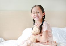 Smiling Asian little girl cuddle teddy bear sitting on the bed at home.  stock photos