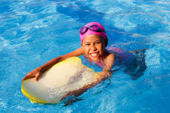 Smiling asian little girl learning to swim in sport pool, practi Royalty Free Stock Image