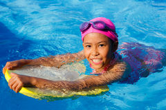 Smiling asian little girl learning to swim in sport pool, practi Royalty Free Stock Images