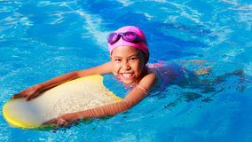 Smiling asian little girl learning to swim in sport pool, practi Stock Photo