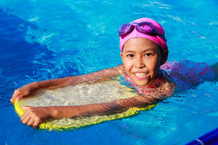 Smiling asian little girl learning to swim in sport pool, practi Royalty Free Stock Photo