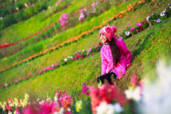 Smiling asian little girl sitting on flower field Stock Images