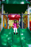 Smiling asian little girl sitting slide. Outdoor portrait Royalty Free Stock Photo