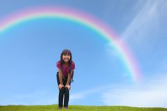 Smiling asian little girl standing on green grass under the rain. Bow, Outdoor Portrait Royalty Free Stock Images