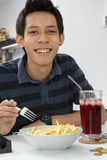 Smiling Asian man eating Stock Photo
