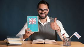 Man is Happy about English. Smiling asian man is happy about english language, wearing gray sweater vest and pristine white shirt, picking up a book and showing stock video footage
