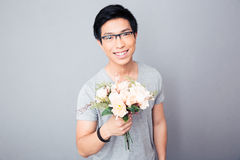 Smiling asian man holding flowers Stock Photos