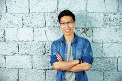 Smiling asian man leaning on brick wall Stock Photography