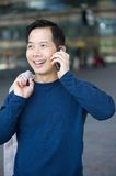 Smiling asian man with mobile phone Royalty Free Stock Image