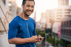 Smiling Asian man preparing a playlist for a city run. Portrait of a smiling young Asian man in sportswear standing outside listening to music on an mp3 player stock photo