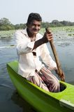 Smiling Asian man row a small traditional boat Stock Photography