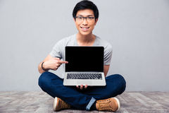 Smiling asian man showing finger on laptop screen Royalty Free Stock Photography