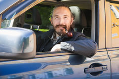 Smiling Asian man smoking pipe. Driver Royalty Free Stock Photo