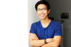 Smiling asian man standing with arms folded Royalty Free Stock Photos