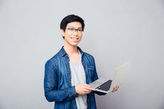 Smiling asian man standing with laptop Royalty Free Stock Images