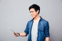 Smiling asian man standing with tablet computer. Over gray background Stock Image