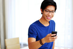 Smiling asian man using smartphone Stock Photo
